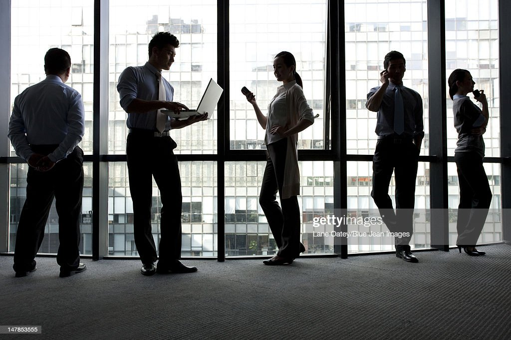 Silhoutte of businesspeople using technology