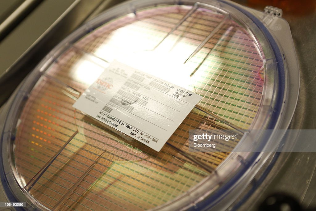 A silicon wafer, a thin slice of semiconductor material used in integrated circuits, is displayed at the headquarters of Broadcom Corp. in Irvine, California, U.S., on Friday, April 12, 2013. Broadcom Corp. is a maker of chips that help mobile devices connect to the Internet. Photographer: Patrick T. Fallon/Bloomberg via Getty Images