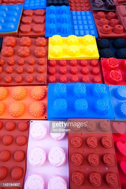 Silicone cake moulds in bright colours on sale at the market in Pienza Tuscany Italy
