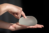 Demonstration of the properties of elasticity, softness, strength, reliability of silicone breast implant, used in plastic surgery to increase or enhance sexuality, aesthetic appeal of formsDemonstrat