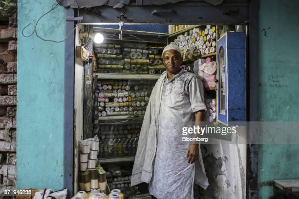 A silk thread vendor poses for a photograph at his store in Varanasi Uttar Pradesh India on Saturday Oct 28 2017 In Varanasi where the manufacture of...