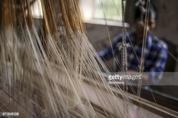 Silk threads hang as a weaver works on a handloom to make a silk saree at a workshop in Varanasi Uttar Pradesh India on Friday Oct 27 2017 In...
