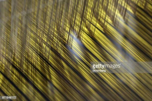 Silk threads of a saree hang from a handloom in a workshop at night in Varanasi Uttar Pradesh India on Saturday Oct 28 2017 In Varanasi where the...