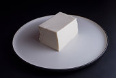 Japanese silken tofu on rustic plate, isolated on black background