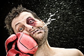 silly boxer man takes a punch in the face isolated on black.funny concept portrait.