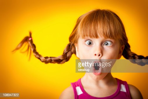 Silly, Red-Haired Girl with Upward Braids Making Crazy Face