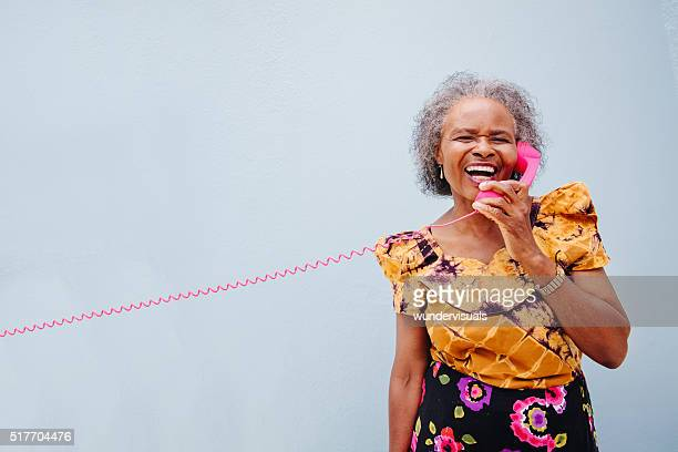 Silly senior woman with pink phone