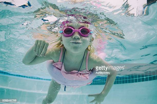 Silly swimming little girl in pool during summer