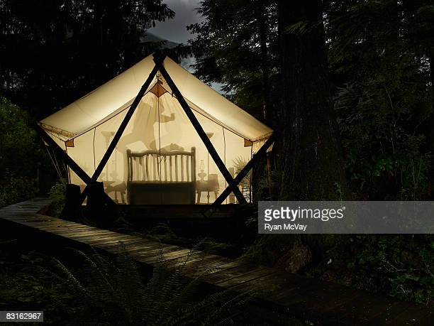 Silouette of woman jumping on bed inside tent.