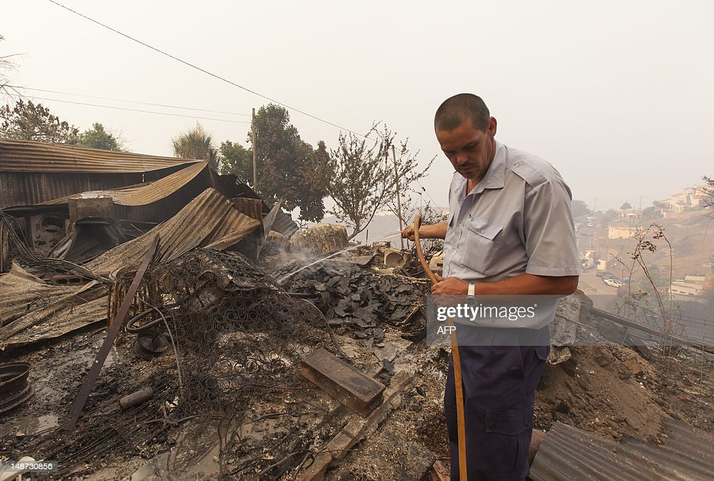 Silva Kent extinguishes the smoldering ashes of a fire that consumed his house in Sao Goncalo, eastern of Funchal, on July 19, 2012. Massive fires broke out in Madeira island leading the evacuation of population in certain regions of the island. A contigent of firefighters plus one C-130 aircraft have been dispatched from mainland Portugal to help tackle the blazes.