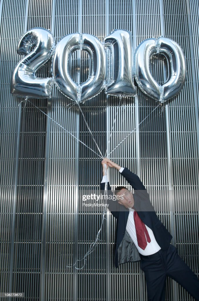 Silver 2010 Balloons Carry Businessman Away : Stock Photo