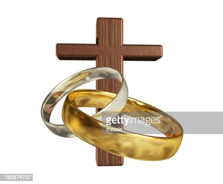 silver and gold wedding rings with a wooden cross stock