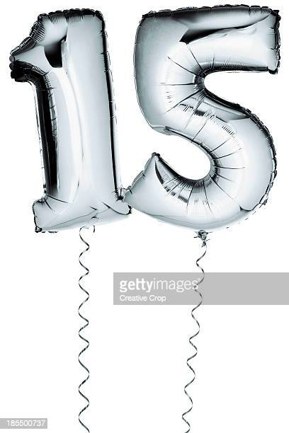 Silver balloons in the shape of a number 15