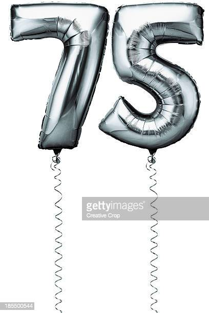 Silver balloons in the shape of a number 75