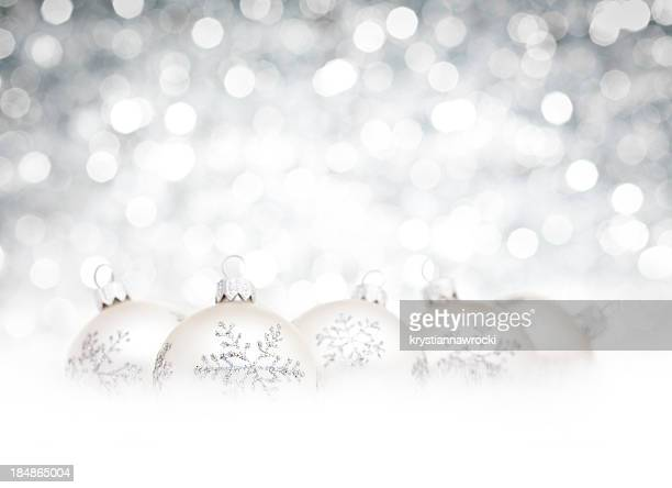 Silver Baubles on snow and white defocused christmas lights