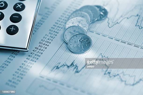silver calculator and coins on sheet of financial data