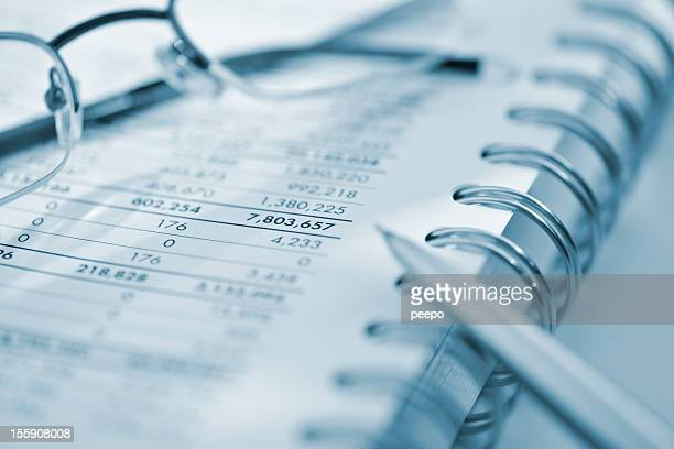 silver calculator and glasses on sheet of financial data
