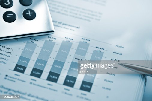 silver calculator and pen on sheet of financial data