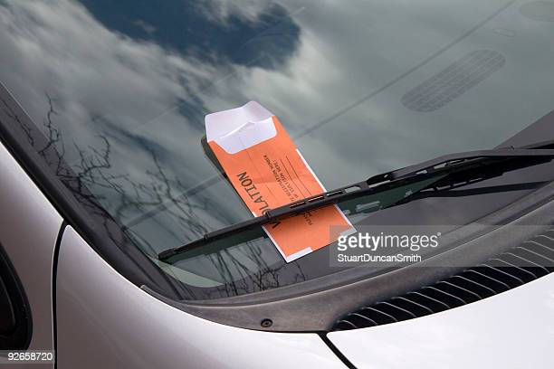 Silver car that has a parking ticket