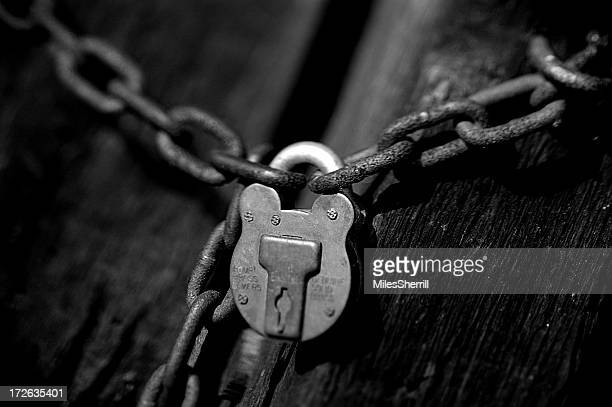 A silver chain connected by a silver padlock on a black door