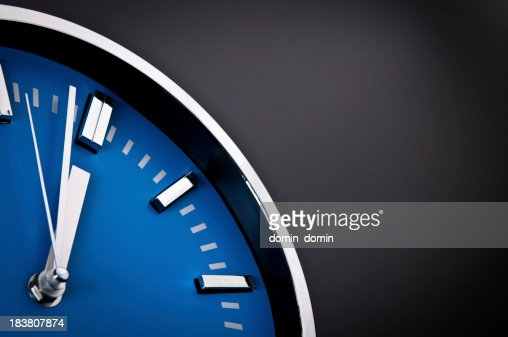 Silver clock with blue clock face showing 11:59