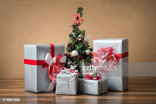 silver colored presents around small christmas tree : Stock Photo