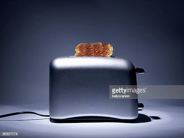 Silver colored toaster with single slice of toast.