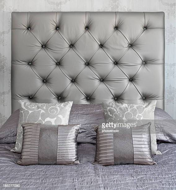 silver coloured silk cushions on a bed