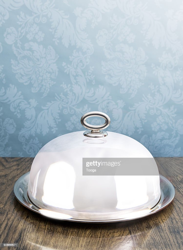 Silver coved serving dish on dining table : Stock Photo