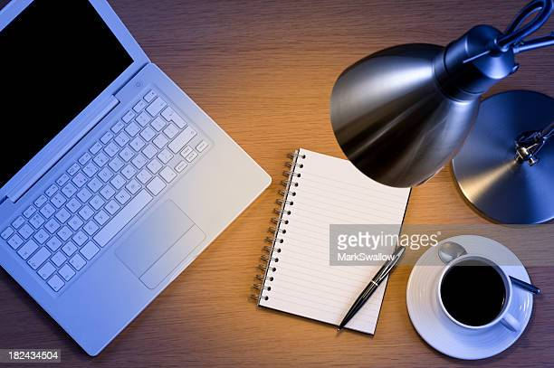 Silver desk lamp laptop pen and notepad and black coffee