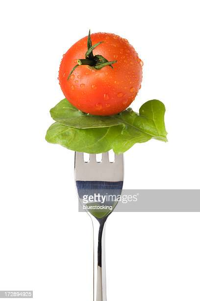 Silver fork holding a salad leaf and fresh-cut tomato