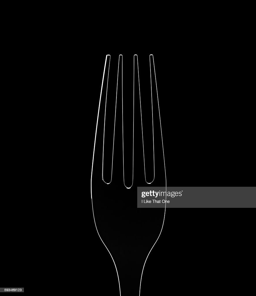 Silver fork rim lit against a black background : Stock Photo