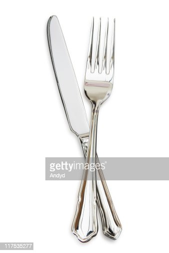 Silver fork sitting across a silver knife