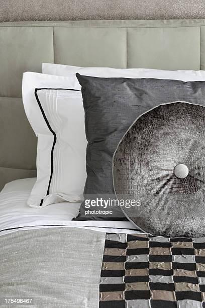 silver grey silk cushions on a bed