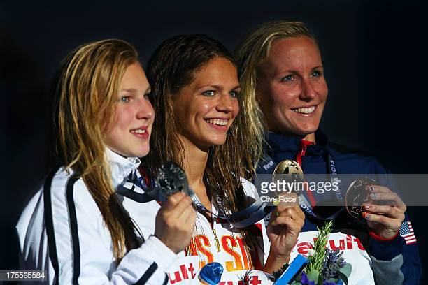Silver medal winner Ruta Meilutyte of Lithuania Gold medal winner Yuliya Efimova of Russia and Bronze medal winner Jessica Hardy of the USA celebrate...