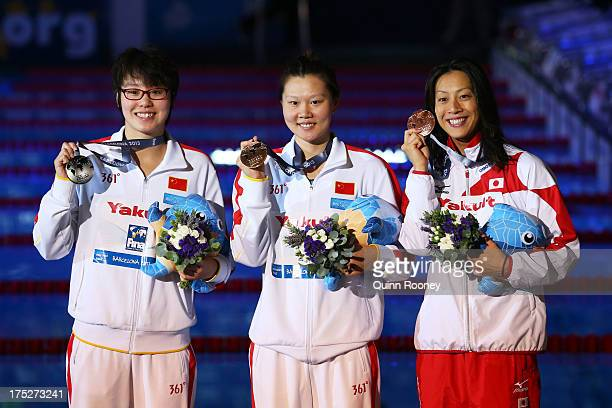 Silver medal winner Yuanhui Fu of China Gold medal winner Jing Zhao of China and Bronze medal winner Aya Terakawa of Japan celebrate on the podium...