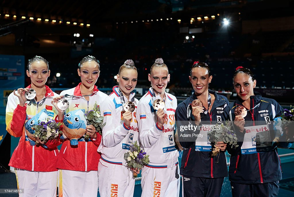 Silver medal winners Jiang Tingting and Jiang Wenwen of China (L), Gold medal winners <a gi-track='captionPersonalityLinkClicked' href=/galleries/search?phrase=Svetlana+Kolesnichenko&family=editorial&specificpeople=7986692 ng-click='$event.stopPropagation()'>Svetlana Kolesnichenko</a> and <a gi-track='captionPersonalityLinkClicked' href=/galleries/search?phrase=Svetlana+Romashina&family=editorial&specificpeople=5988166 ng-click='$event.stopPropagation()'>Svetlana Romashina</a> of Russia (C), and bronze medal winners Carbonell Ballestero and <a gi-track='captionPersonalityLinkClicked' href=/galleries/search?phrase=Margalida+Crespi&family=editorial&specificpeople=9591397 ng-click='$event.stopPropagation()'>Margalida Crespi</a> Jaume of Spain celebrate on the podium after the Synchronized Swimming Duet Free Final on day six of the 15th FINA World Championships at Palau Sant Jordi on July 25, 2013 in Barcelona, Spain.