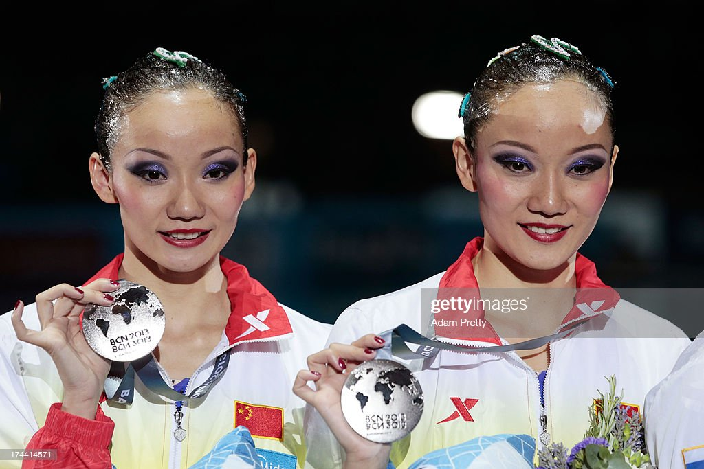 Silver medal winners Jiang Tingting and Jiang Wenwen of China celebrate on the podium after the Synchronized Swimming Duet Free Final on day six of the 15th FINA World Championships at Palau Sant Jordi on July 25, 2013 in Barcelona, Spain.