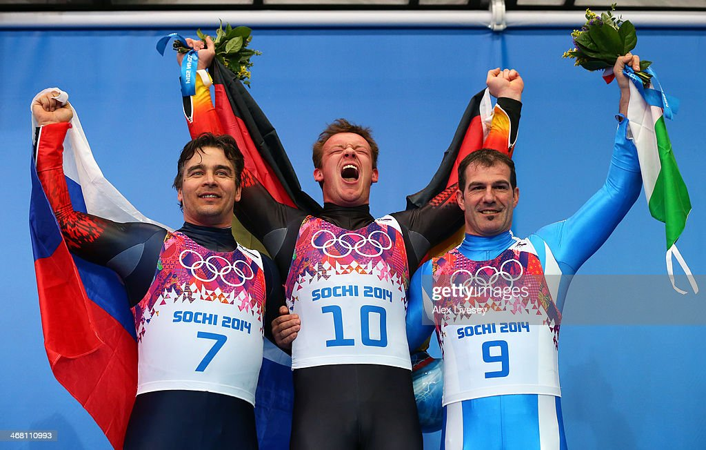 Silver medalist Albert Demchenko of Russia, gold medalist <a gi-track='captionPersonalityLinkClicked' href=/galleries/search?phrase=Felix+Loch&family=editorial&specificpeople=4840944 ng-click='$event.stopPropagation()'>Felix Loch</a> of Germany and bronze medalist <a gi-track='captionPersonalityLinkClicked' href=/galleries/search?phrase=Armin+Zoeggeler&family=editorial&specificpeople=227382 ng-click='$event.stopPropagation()'>Armin Zoeggeler</a> of Italy on the podium during the flower ceremony for the Men's Luge Singles on Day 2 of the Sochi 2014 Winter Olympics at Sliding Center Sanki on February 9, 2014 in Sochi, Russia.