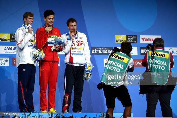 Silver medalist Aleksandr Krasnykh of Russia gold medalist Yang Sun of China and bronze medalist Townley Haas of the United States pose with the...