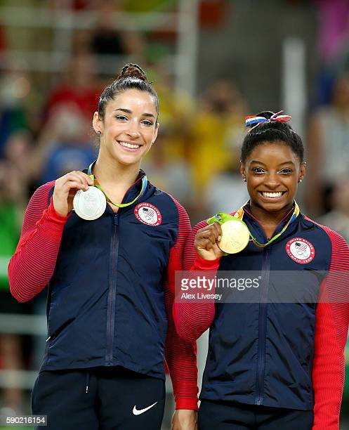 Silver medalist Alexandra Raisman and gold medalist Simone Biles of the United States pose for photographs on the podium at the medal ceremony for...