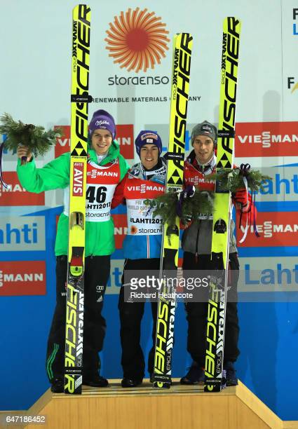 Silver medalist Andreas Wellinger of Germany gold medalist Stefan Kraft of Austria and bronze medalist Piotr Zyla of Poland pose during the flower...