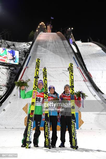 Silver medalist Andreas Wellinger of Germany gold medalist Stefan Kraft of Austria and bronze medalist Piotr Zyla of Poland pose after the flower...