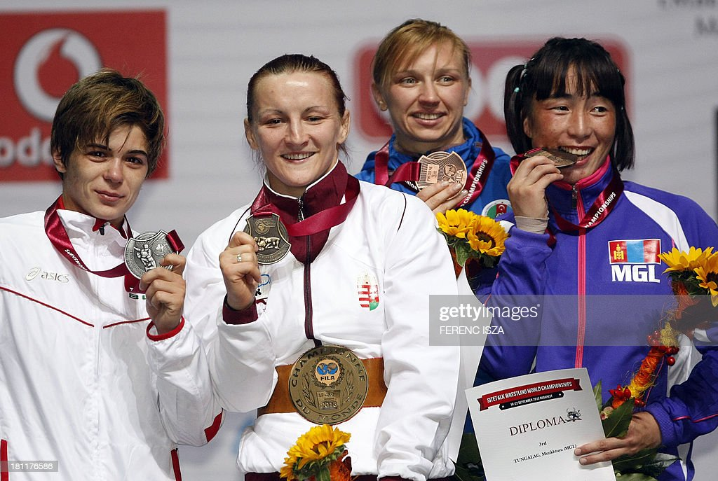 Silver medalist Bulgaria's Taybe Mustafa Yusein (L), gold medalist Hungary's Marianna Sastin (2ndL), bronze medalist Azerbaidzan's Yuliya Ratkevich (2ndR) and bronze medalist Mongolia's Munkhtuya Tungalag (R) celebrate on the podium of the women's free style 59 kg category of the World Wrestling Championships in Budapest on September 19, 2013. AFP PHOTO / FERENC ISZA