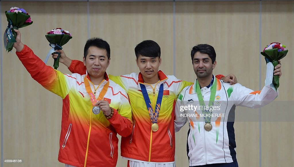 Silver medalist China's Cao Yifei gold medalist China's Yang Haoran and bronze medalist India's Abhinav Bindra pose after the medal ceremony of the...