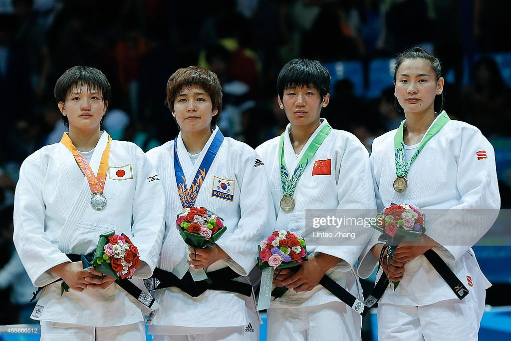 Silver medalist <a gi-track='captionPersonalityLinkClicked' href=/galleries/search?phrase=Chizuru+Arai&family=editorial&specificpeople=11700769 ng-click='$event.stopPropagation()'>Chizuru Arai</a> of Japan, Gold medalist Jaebum Kim of South Korea, Bronze medalist Fei Chen of China and Naranjargal Tsend Ayush of Mongolia celebrate during the medal ceremony after the Women's -70 kg Final at Dowon Gymnasium during day two of 2014 Asian Games on September 21, 2014 in Incheon, South Korea.