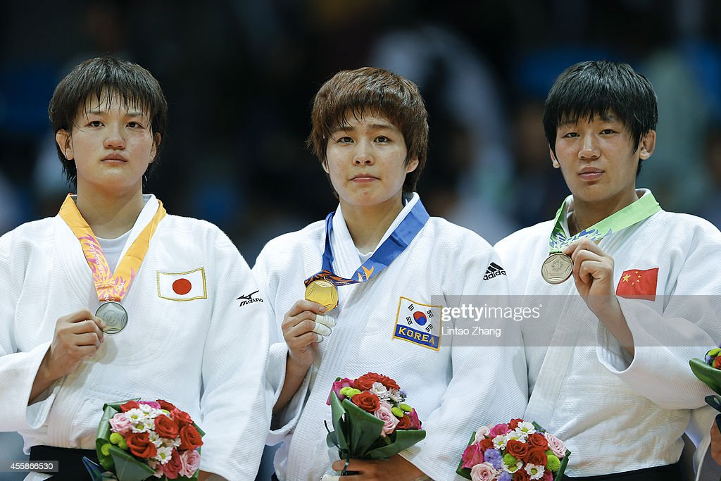 Silver medalist <a gi-track='captionPersonalityLinkClicked' href=/galleries/search?phrase=Chizuru+Arai&family=editorial&specificpeople=11700769 ng-click='$event.stopPropagation()'>Chizuru Arai</a> of Japan, Gold medalist Jaebum Kim of South Korea and Bronze medalist Fei Chen of China celebrate during the medal ceremony after the Women's -70 kg Final at Dowon Gymnasium during day two of 2014 Asian Games on September 21, 2014 in Incheon, South Korea.