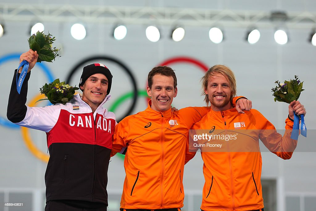 Silver medalist <a gi-track='captionPersonalityLinkClicked' href=/galleries/search?phrase=Denny+Morrison&family=editorial&specificpeople=726041 ng-click='$event.stopPropagation()'>Denny Morrison</a> of Canada, gold medalist <a gi-track='captionPersonalityLinkClicked' href=/galleries/search?phrase=Stefan+Groothuis&family=editorial&specificpeople=889680 ng-click='$event.stopPropagation()'>Stefan Groothuis</a> of the Netherlands and bronze medalist <a gi-track='captionPersonalityLinkClicked' href=/galleries/search?phrase=Michel+Mulder&family=editorial&specificpeople=8699903 ng-click='$event.stopPropagation()'>Michel Mulder</a> of the Netherlands celebrate during the flower ceremony for the Men's 1000m Speed Skating event during day 5 of the Sochi 2014 Winter Olympics at at Adler Arena Skating Center on February 12, 2014 in Sochi, Russia.