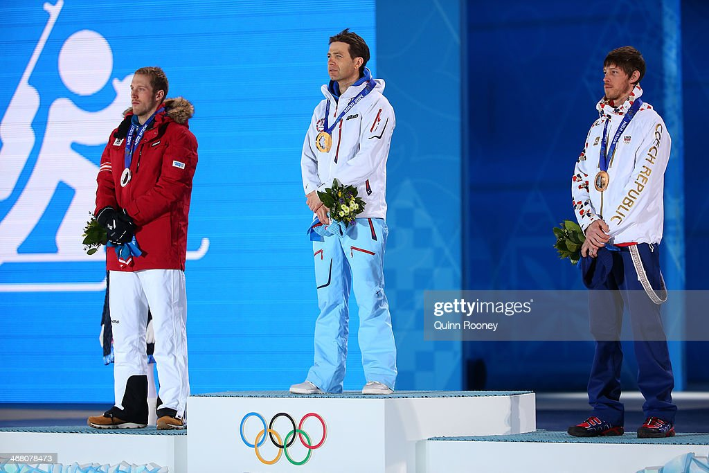 Silver medalist <a gi-track='captionPersonalityLinkClicked' href=/galleries/search?phrase=Dominik+Landertinger&family=editorial&specificpeople=4698843 ng-click='$event.stopPropagation()'>Dominik Landertinger</a> of Austria, gold medalist <a gi-track='captionPersonalityLinkClicked' href=/galleries/search?phrase=Ole+Einar+Bjoerndalen&family=editorial&specificpeople=206663 ng-click='$event.stopPropagation()'>Ole Einar Bjoerndalen</a> of Norway and bronze medalist Jaroslav Soukup of the Czech Republic stand for the national anthem on the podium during the medal ceremony for the Men's Sprint 10 km on day 2 of the Sochi 2014 Winter Olympics at Medals Plaza on February 9, 2014 in Sochi, .