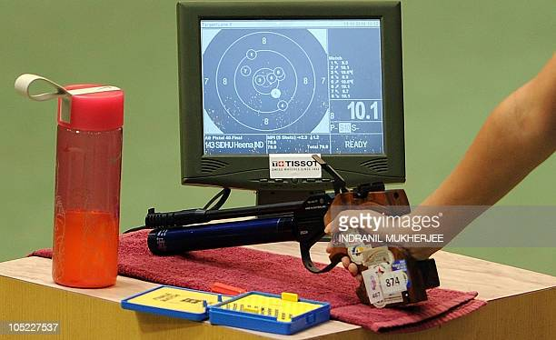 Silver medalist Heena Sidhu of India rests her hand by the monitor showing her score in the women's singles 10m air pistol event of the XIX...